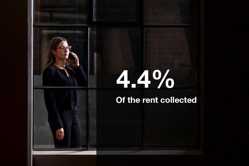 Business person using phone outside through window